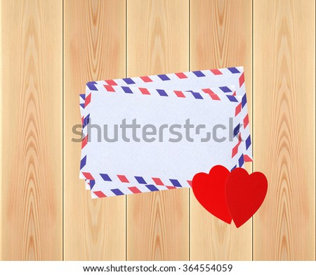 Stack of letters and two red hearts on rustic wooden planks background