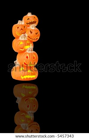 Stack of Lighted Halloween Pumpkins - A carved jack o lantern pumpkin stack isolated and reflected on black with space for copy. - stock photo