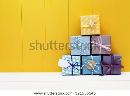 Stack of little present boxes on yellow wooden wall - stock photo