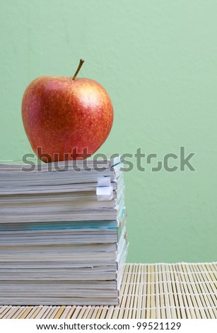 Stack of magazines and apple - stock photo