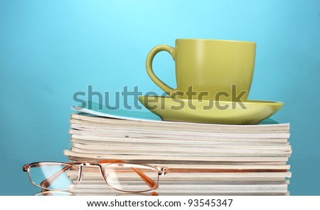 stack of magazines, cup and glasses on blue background - stock photo