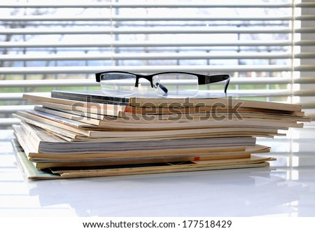 Stack of magazines in front of office window