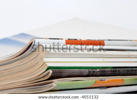 Stack of magazines on table in white background - stock photo