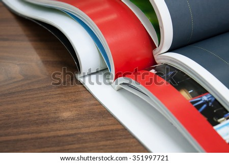 Stack of magazines on wood table - stock photo