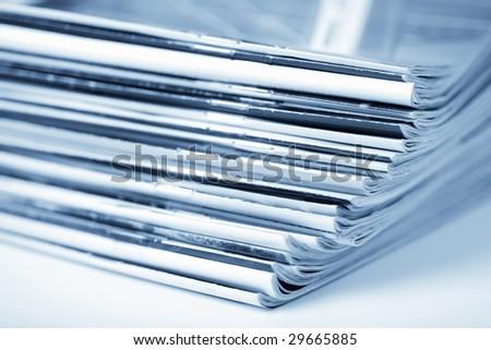 stack of magazines toned blue isolated - stock photo