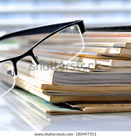 Stack of magazines with glasses - stock photo