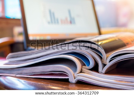 Stack of magazines with report on laptop, blur coffee shop background  - stock photo