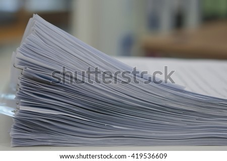 Stack of many  document organized by clipping placed on desk in office.