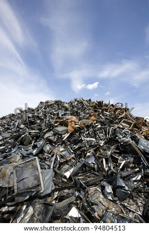 Stack of Metal Garbage in front of blue sky - stock photo