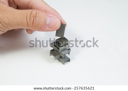 Stack of metal staples, with hand, Isolated on a white background. - stock photo