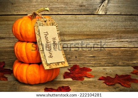 Stack of mini pumpkins with Happy Thanksgiving tag on a wooden background        - stock photo