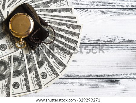 Stack of money dollars laid out like a fan with antique gold watch on white retro stylized wood background - stock photo