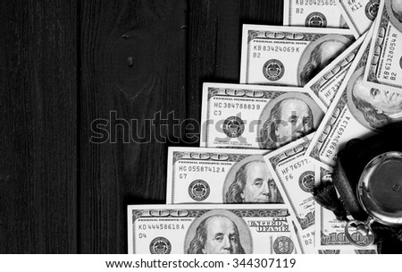 Stack of money dollars laid out like a ladder with antique gold watch on black retro stylized wood background black and white - stock photo
