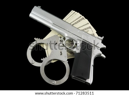 Stack of money, gun and handcuffs isolated on black - stock photo