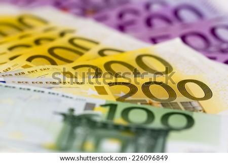 Stack of money with 100 focused 200 and 500 euro banknotes. Perfect for illustrating e.g. wealth, lottery prizes or banking crises. What is your dream? - stock photo