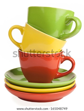 stack of multicolored tea cups and saucers, isolated on white