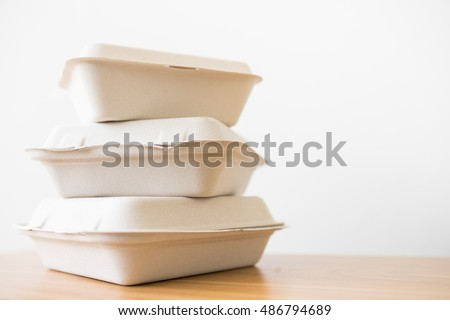 Stack of natural plant fiber food box on wooden background.