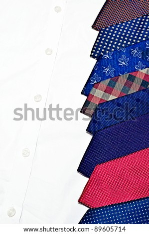 Stack of neck ties on white buttoned shirt - stock photo