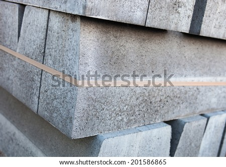 Stack of new concrete blocks tied-up with plastic stripe. - stock photo