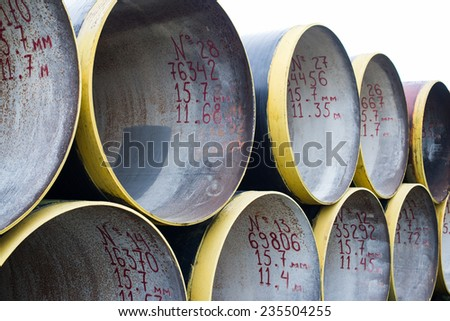 Stack of new metal pipes with yellow-painted edges. - stock photo