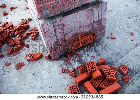 Stack of new silicate bricks in misted polyethylene with the piles of beaten bricks nearby. - stock photo