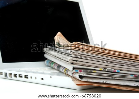 stack of newspaper next to a laptop - stock photo