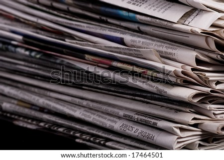 Stack of newspaper on black background close up - stock photo