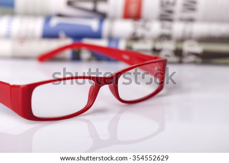 Stack of newspapers and glasses - stock photo