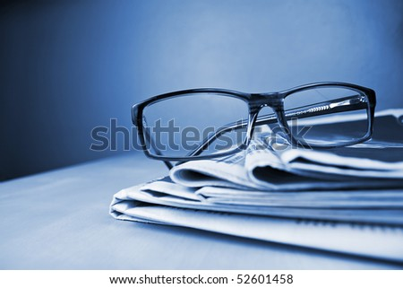 Stack of newspapers and glasses blue toned - stock photo
