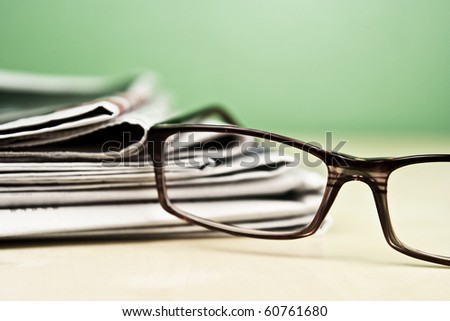 Stack of newspapers and glasses lying on table desaturated - stock photo