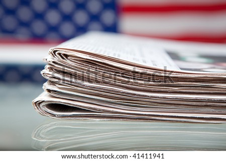 stack of newspapers before the ensign of the USA