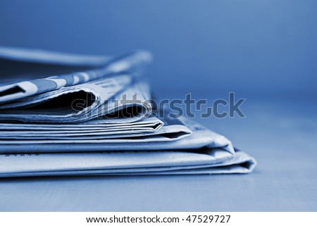 Stack of newspapers blue toned - stock photo