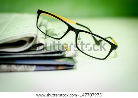 Stack of newspapers & glasses on table.