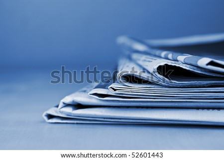 Stack of newspapers lying on the table blue toned
