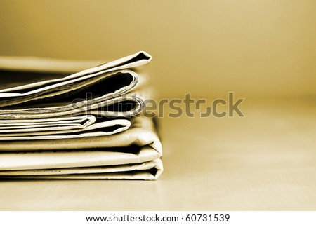 Stack of newspapers lying on the table sepia toned