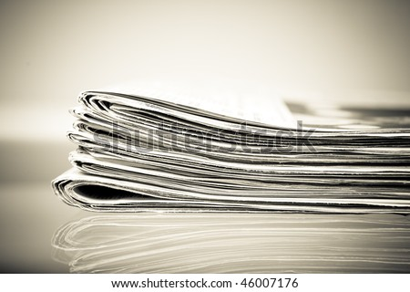 stack of newspapers on a glass table, vintage image - stock photo