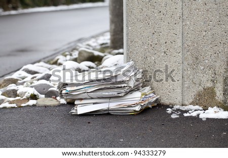 stack of newspapers on a winter street