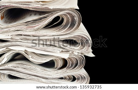 stack of newspapers on black - stock photo