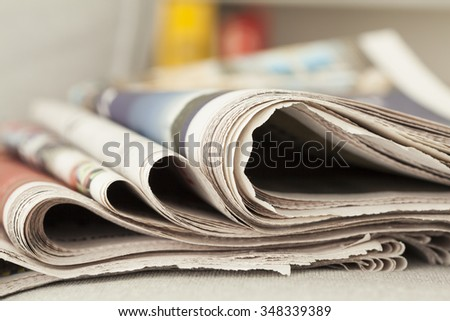 Stack of newspapers on table - stock photo