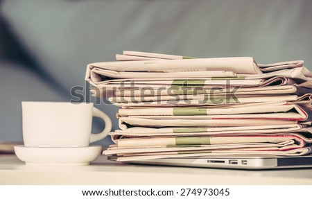Stack of newspapers with a cup of coffee, vintage edition - stock photo