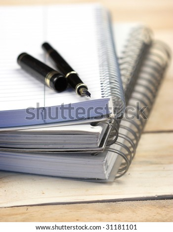 stack of notebooks and pen,shallow dof