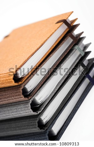Stack of notebooks  with color cover over white