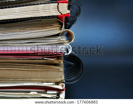 Stack of office folders on black wall