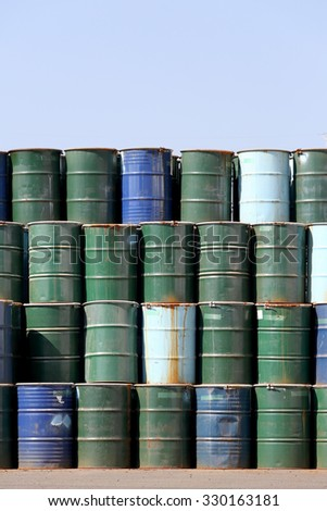 stack of oil barrels against a  blue sky - stock photo