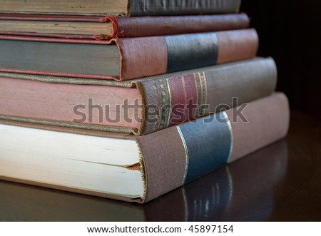stack of old antique books on library table, shallow depth of field - stock photo