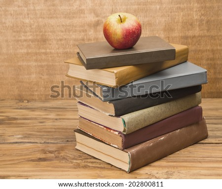 Stack of old books and apple on rustic wooden table