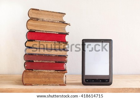 Stack of old books and e-book lying on wooden shelf   - stock photo