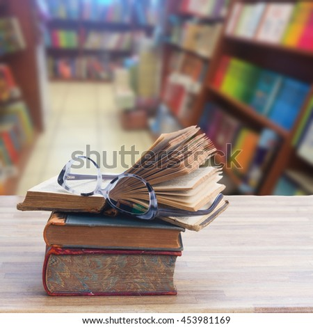 Stack of old books and glasses on wooden table desktop in bookstore - stock photo