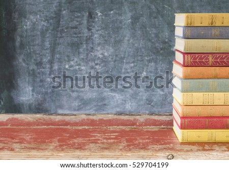stack of old books,in front of a black board, excellent copy space
