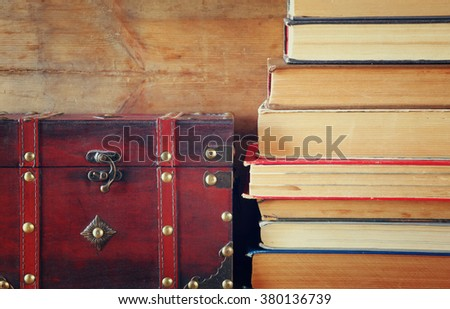 stack of old books next to antique wooden chest on wooden shelf  - stock photo